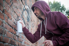 Hooded tagger writing graffiti on urban walls Royalty Free Stock Photo