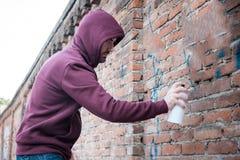 Hooded tagger writing graffiti on urban walls Royalty Free Stock Photo