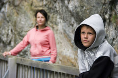 Hooded teenage boy. A teenage boy wearing a hood over his head, mother in the background Royalty Free Stock Photography