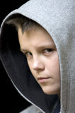 Hooded teenage boy. Portrait of a young teenage boy wearing a hood, isolated on black background. Serious expression on his face Stock Photography