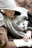 Hooded teenage boy reads book Stock Photography
