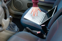 Hooded thief stealing a computer laptop from a parked car stock image