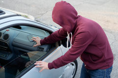 Hooded thief stealing a phone smart phone from a parked car royalty free stock photography