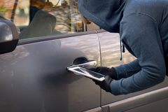 Free Hooded Thief Tries To Break The Car`s Security Systems With Tablet Stock Image - 163277711