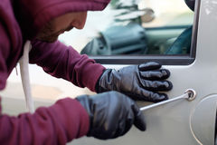 Hooded thief trying to open a car Royalty Free Stock Photo