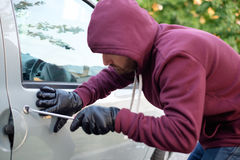 Hooded thief trying to open a car door lock Stock Image