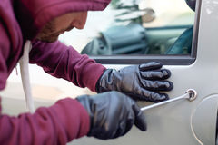 Hooded thief trying to open a car door lock steal Stock Image