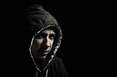 Hooded thug. Low key portrait of a hooded thug staring Stock Images