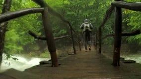 Hooded Tourist Walking On Bridge Hanging Above stock video