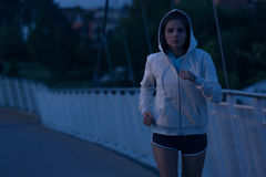 Hooded woman running in the park at night. Hooded young woman running by night in the park. Fitness and workout wellness concept. Sports outdoors. Cityscape Stock Photo