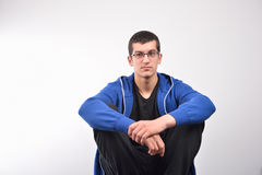 Hooded young man sitting against a wall Stock Photos