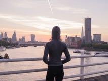 Hoodie молодой женщины нося на мосте в Лондоне на восходе солнца Стоковая Фотография RF