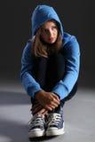 单独白肤金发的蓝色女孩hoodie哀伤的少&#24 免版税图库摄影