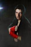 Молодой человек в шлямбуре hoodie бокса при изолированный клобук на головной нося руке и обернутое запястьем руки готовое для вою Стоковое Изображение RF