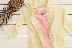 Hoodie jaune et un T-shirt, ananas Vieux fond en bois blanc Photos libres de droits