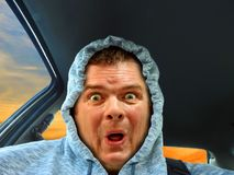 Hoodie outraged driver. Photo of a hoodie driver with outraged looking expression on face Stock Photography