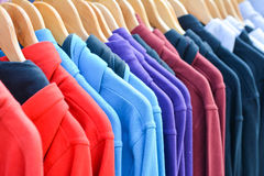 Hoodies in a row. A row of hooded tops hanging uniformly on a rail Stock Photography