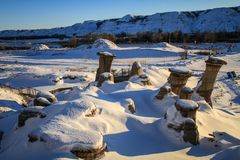 The hoodoos of drumheller during a sunny frosty winter day, drumheller, badlands of Alberta, Alberta, Canada. A hoodoo also called a tent rock, fairy chimney or stock photography
