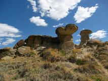 Dramatic Rock Formations in Dinosaur Provincial Park, Alberta. These hoodoos with their large mushroom capstones are sights in the arid badlands along the Red royalty free stock photo