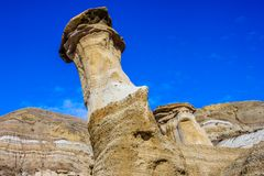 Lone hoodoo standing at attention. Hoodos, Willow Creek Trail, Cambria, Alberta, Drumheller, Alberta, Canada with a bright blue sky stock photos