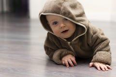 hoody棕色的毛皮的逗人喜爱的9个月孩子沿某事的胳膊做 免版税库存照片