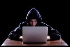 黑暗的hoody开会的黑客在笔记本前面 免版税图库摄影