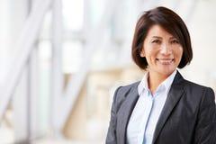 Hoofd en schoudersportret van glimlachende Aziatische onderneemster royalty-vrije stock fotografie
