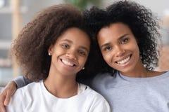 Hoofd geschoten portret van gelukkige Afrikaanse Amerikaanse moeder en dochter royalty-vrije stock afbeelding