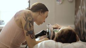 Hoofd het maken tatoegering voor vrouw die tatoeërend machine in salon, zijaanzicht gebruiken stock videobeelden