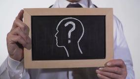 Hoofd met questionmark op bord in artsenhanden wordt getrokken, diagnostiek die stock video