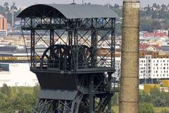 Hoofd van de mijnbouwtoren en een schoorsteen met het centrum van Ostrava op de achtergrond Stock Foto