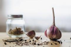 Hoofd van knoflook, zwarte peperbollen, komijnzaden, laurierbladeren en een kruik van kruiden op een lichte houten lijst stock foto's