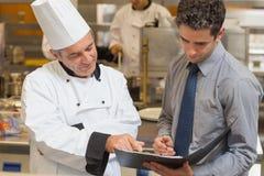 Hoofdchef-kok en kelner die menu bespreken Stock Afbeelding