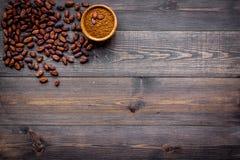 Hoofdingrediënt voor chocolade Cacaopoeder in kom dichtbij cacaobonen op de donkere houten ruimte van het achtergrond hoogste men Stock Foto's