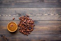 Hoofdingrediënt voor chocolade Cacaopoeder in kom dichtbij cacaobonen op de donkere houten ruimte van het achtergrond hoogste men Stock Fotografie