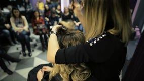 Hoofdklasse in de kunst van het kappen, model, en heel wat studenten van kappers op de achtergrond stock footage