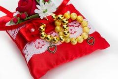 Hoofdkussen met de gouden ringen van de parelsarmband Stock Foto