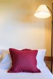 Hoofdkussen op een bed en een lamp Stock Afbeeldingen