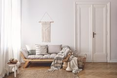 Hoofdkussens en deken op houten bank in wit zolderbinnenland met deur en lijst aangaande tapijt Echte foto stock foto