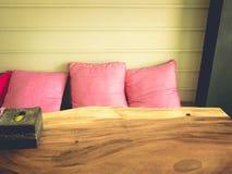 3 hoofdkussens en houten lijst stock foto