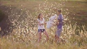 Hoofdkussenstrijd Het jonge paar heeft gek pret Een vrouw slaat haar hoofdkussen met een vriend stock videobeelden