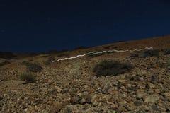 Hoofdlamp lichte sleep op vulkaan Teide stock afbeeldingen