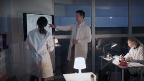 Hoofdmachinist die details van onderzoek verklaren aan zijn collega in laboratorium stock footage