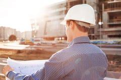 Hoofdmachinist met tekening het in hand bekijken de bouwwerf Mening van de rug Stock Afbeelding