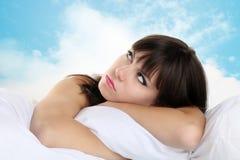 Hoofdmeisje op hoofdkussen met blauwe hemel op achtergrond Royalty-vrije Stock Afbeelding