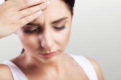 Hoofdpijn in een jong meisje migraine Moeheid na een harde werkdag Het concept gezondheid op een grijze achtergrond Royalty-vrije Stock Afbeeldingen
