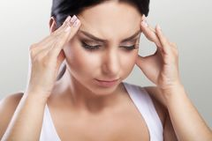 Hoofdpijn in een jong meisje migraine Moeheid na een harde werkdag Het concept gezondheid op een grijze achtergrond Stock Fotografie