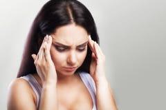 Hoofdpijn in een jong meisje migraine Moeheid na een harde werkdag Het concept gezondheid op een grijze achtergrond Royalty-vrije Stock Foto