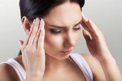 Hoofdpijn in een jong meisje migraine Moeheid na een harde werkdag Het concept gezondheid op een grijze achtergrond Stock Afbeeldingen