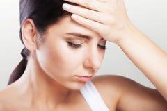 Hoofdpijn en strenge spanning ervaring Pijnlijk gevoel in het hoofd moeheid Het concept gezondheid op een grijze achtergrond Stock Afbeelding